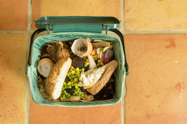 Indoor food recycling caddy full of kitchen waste including meat and bread (which can't be composted at home) to be collected as part of a local food waste recycling service.