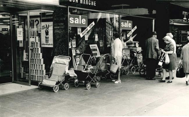 Bulky prams and pushchairs parked outside the new Bon Marche department store about half a century ago