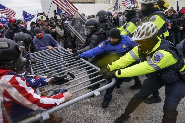 Swindon Advertiser: Trump supporters try to break through a police barrier at the Capitol in Washington on Wednesday Picture: AP Photo/John Minchillo