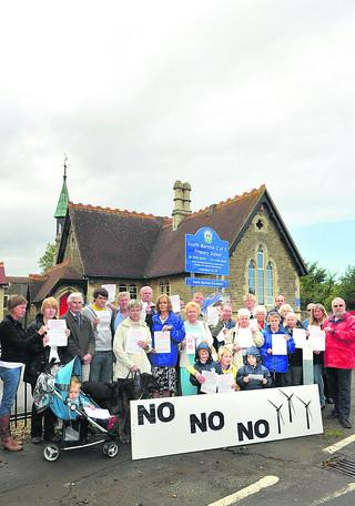 South Marston anti-turbine protesters gather outside the primary school. The proposed Honda turbines will be visible behind the school