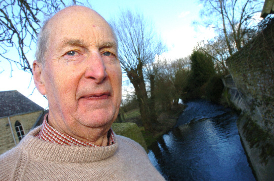 Seymour Aitken beside the River Thames which would be diverted if the canal is restored