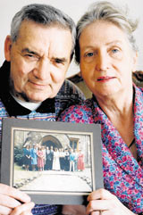 Sean and Christeen Norris pictured in 1994 with a photograph of their 14 children. Sean, a champion wrestler, singer and author, died aged 77 on Sunday