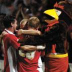 Swindon Advertiser: Jack Smith is mobbed by Lee Peacock, Andy Caton and club mascot Rockin' Robin after levelling the match from the penalty spot last night Ref: 203874-58
