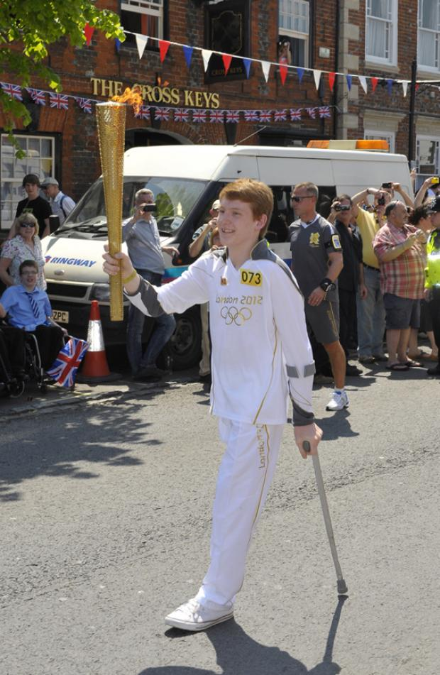 Ben Fox carries the Olympic Flame through Royal Wootton Bassett