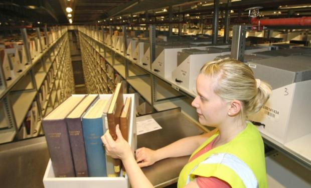 Warehouse assistant Kelci Finucane with some of the 7.5 million books