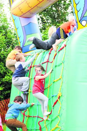 Children scale the walls of the bouncy castle