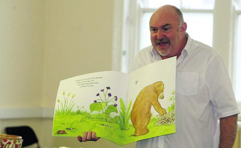 Author Neil Griffiths pictured telling a story to children at the Swindon central library