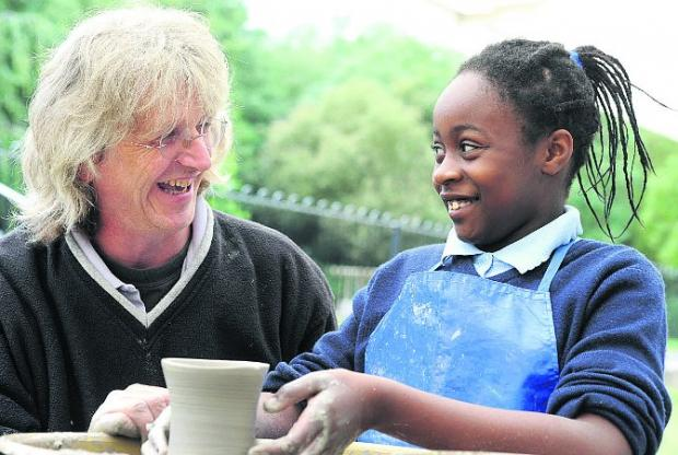 HELPING HAND  Artist Neil Alcock shows pupil Sammy how to use the potter's wheel Picture: SIOBHAN BOYLE