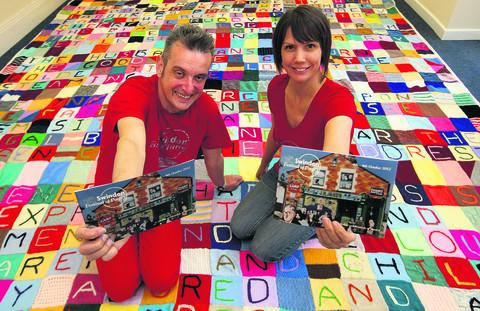 Michael Scott and Hilda Sheehan at the start of the Swindon Festival Of Poetry. They are sitting on a patchwork carpet made by the friends of Alfred Williams