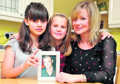 Liz Dabner with her daughters Grace, 12, and Jasmine, nine, and a picture of Derek
