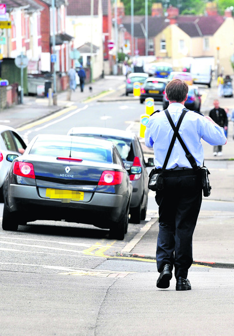 A parking warden on patrol in in the town centre