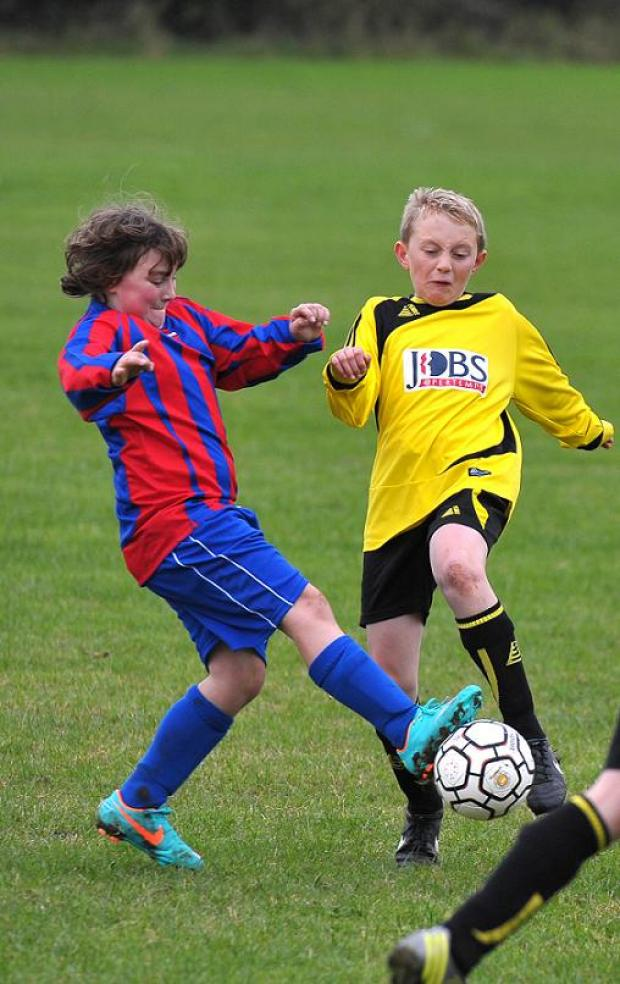 Tommy Elsworth, left, and Jay Basford go in for a tackle during the clash between Shaw Under 13s and Croft Under 13s