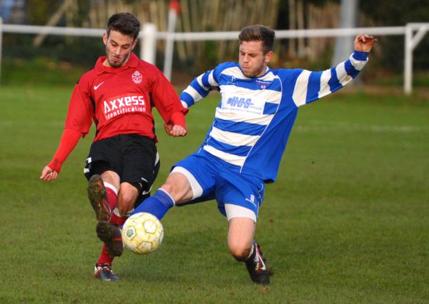 Shrivenham's Taylor Gill gets his boot in ahead of Highworth's Ryan King
