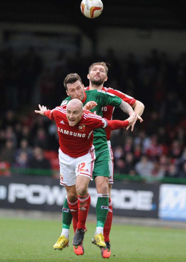 Swindon Town's Darren Ward and Alan McCormack combine to win a header