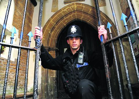 PC Lee Kuklinski at St Sampson's Church, in Cricklade, where headstones and railings were damaged and a burglary took place