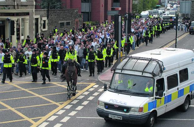 IN THE LINE OF DUTY Police escort Millwall football fans for a match against Swindon Town at Swindon County Ground