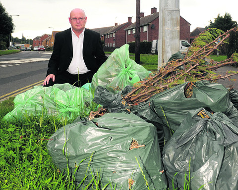 Coun Jim Grant with a backlog of green waste last September