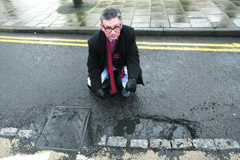 Councillor Derique Montaut in Princes Street Swindon which has some nasty potholes