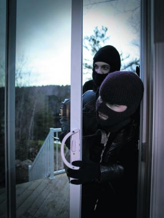 Two burglars entering a home. Pictured posed by models