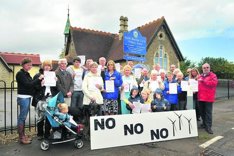 South Marston anti-turbine protesters gather outside the primary school. The proposed Honda turbines were set to be visible behind the school