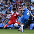 Swindon Advertiser: Tijane Reis, left, blocks a clearance from Posh's Craig Alcock