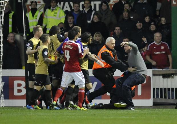 Andrew Bowles is wrestled to the floor by stewards following pitch invasion and assault.