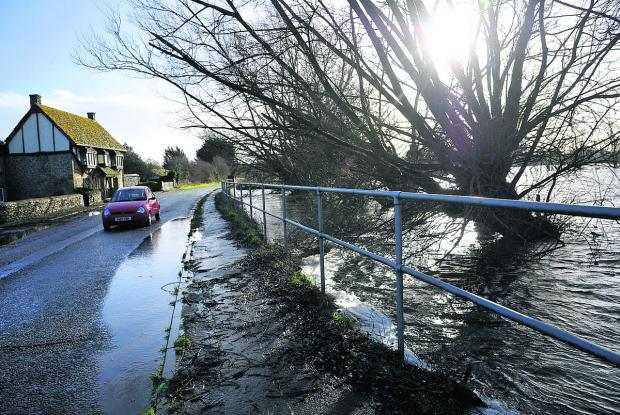 A motorist proceeds with  caution as rainwater threatens to flood a road near Cricklade