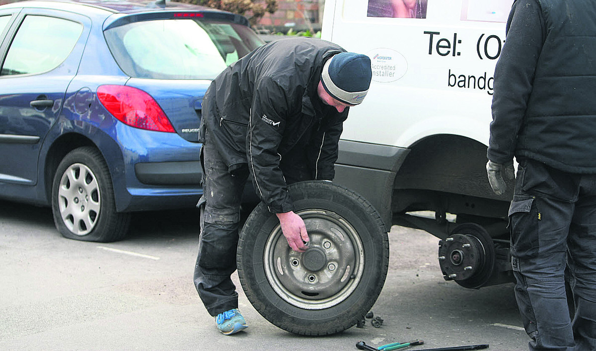 Andy Noton changes a tyre in Dixon Street after hundreds of were slashed overnight on cars and vans in the Old Town area last February