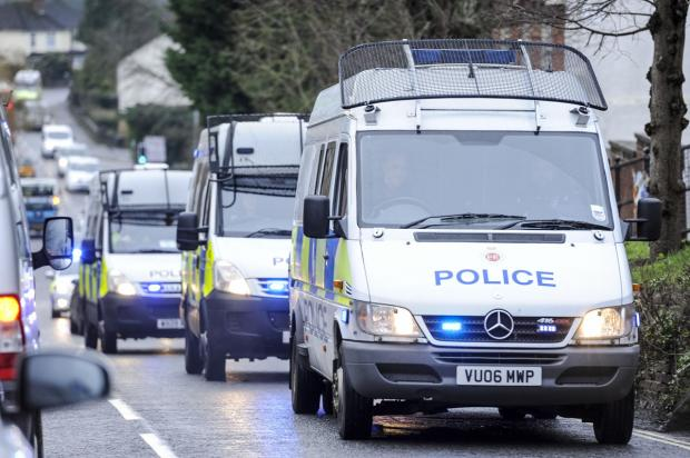 A police convoy rolls out ahead of today's drugs raids