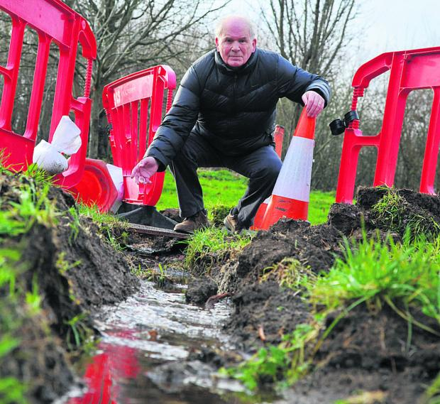 Before maintenance on the Liden Drive footpath, residents including John McClay got out their shovels to dig a trench to chanel away floodwater. Residents say the issue has still not been resolved