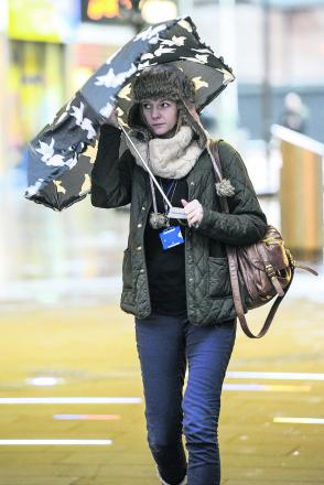 A shopper braves the wet and windy weather in Swindon Town Centre