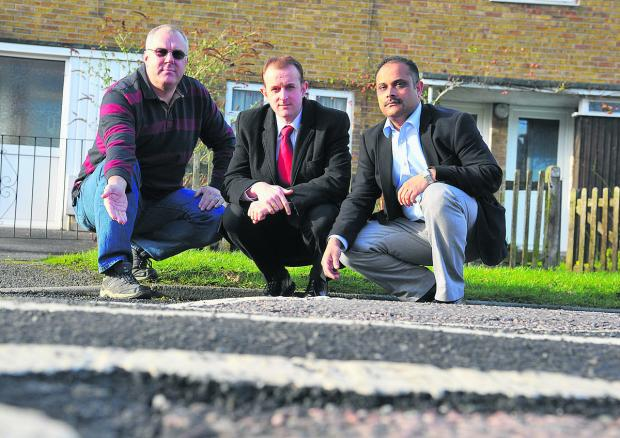 Resident Glenn Stanley, right, Labour group deputy leader Mark Dempsey, left, and Walcot councillor Abdul Amin inspecting the damage to the road in Kingswood Avenue