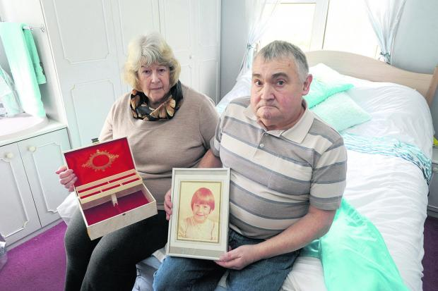 Anne and Peter Sinfield, from Brandenstoke, whose home was broken into. Anne is holding her empty jewellery box and Peter a picture of their daughter Karen, who died of cancer aged eight