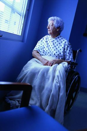 Female patient sitting in a wheelchair looking out of a window       Picture: Posed by a model
