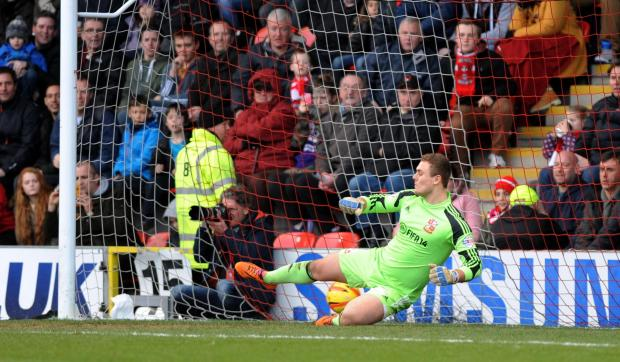 Swindon Advertiser: Swindon Town's Tyrell Belford is sent the wrong way from the spot by Leyton Orient's Lloyd James