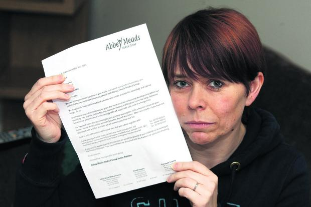 Mum of nine Michelle Martin with the letter she received from Abbey Meads Medical Practice