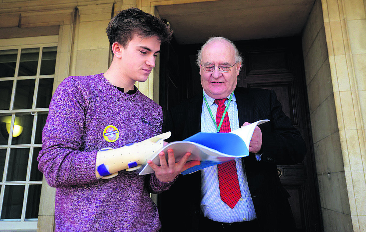 Chris Baker, a volunteer at Salisbury's Grosvenor House youth centre hands a petition to Coun Richard Gamble