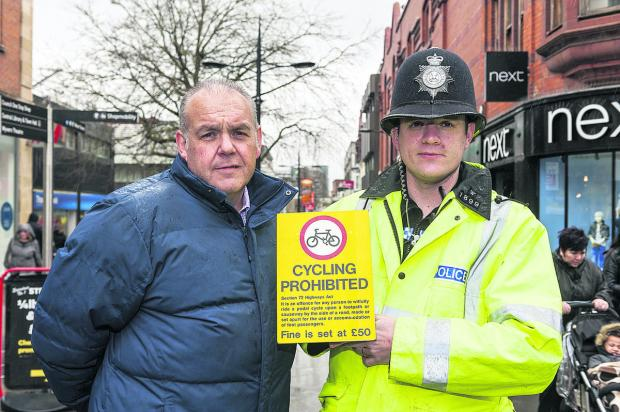 Anti-social behaviour investigator Jerry Law and Community Beat Manager PC Paul Bezzant  with the additional signs  being  put up in the town centre telling people not to cycle there