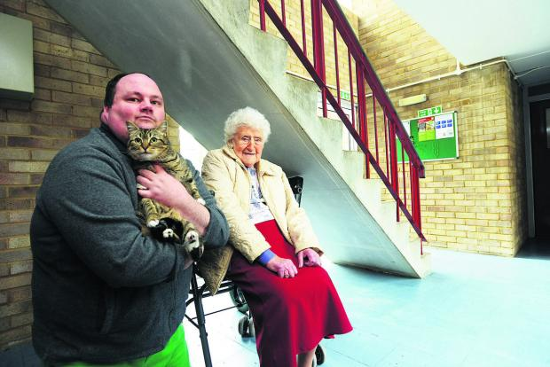 Doris Turner in the space under the stairs where she keeps her wheelchair, which is now deemed to be a fire risk. With her is Philip Dunn with his cat Sally. He has also been told he cannot keep the animal because she is a fire risk