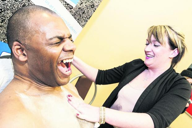 Leroy Robinson,  the manager of Tesco in  Ocotal Way, getting his chest waxed by Samantha McHugh as part of the store's fundraising for Diabetes UK