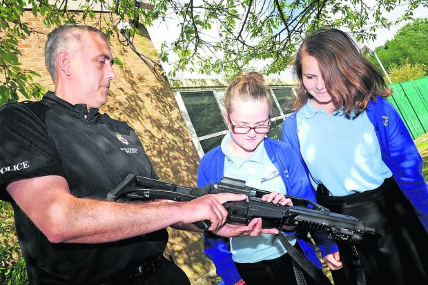 PC Shaun Dodson shows Dorcan Academy pupils Emily Miles and Lauren Rogers a firearm in a bid to make pupils aware of the dangers and, below, swords seized during the Ope
