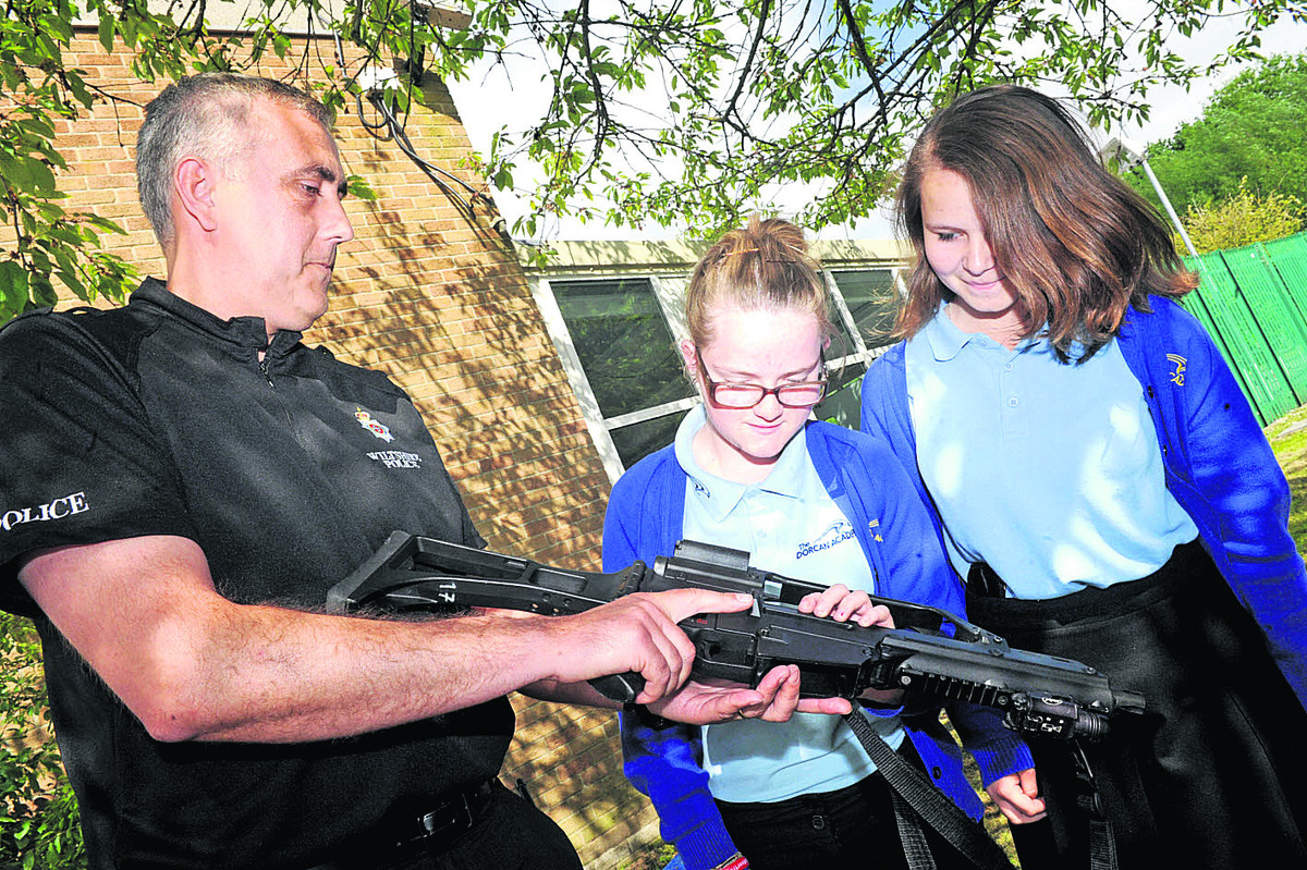 PC Shaun Dodson shows Dorcan Academy pupils Emily Miles and Lauren Rogers a firearm in a bid to make pupils aware of the dangers and, below, swords seized during the Operation Harness day of action in January