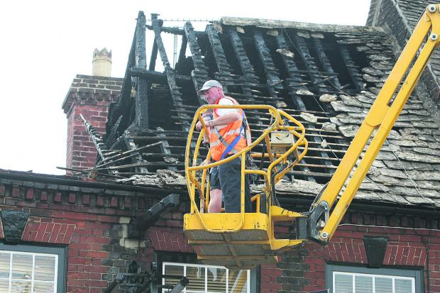Inspecting the charred remains of the Cross Key's roof following last July's devastating fire. The pub is now due to be repaired
