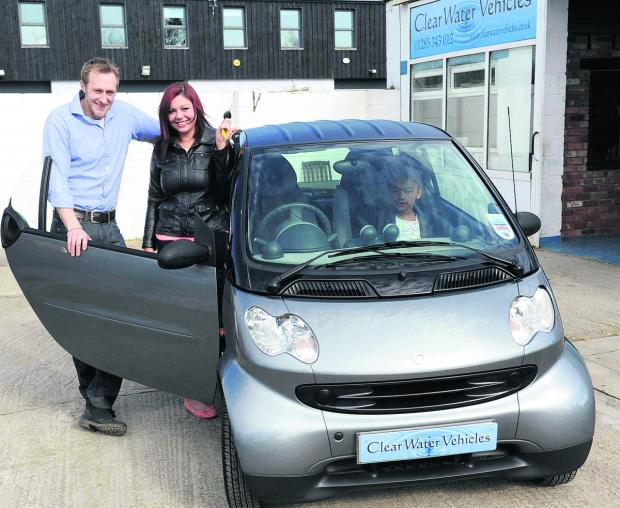 Swindon Advertiser: Richard King, from Clear Water Vehicles, hands over the keys to a Smart Car to Hayley Gooden as his Random Act Of Kindness