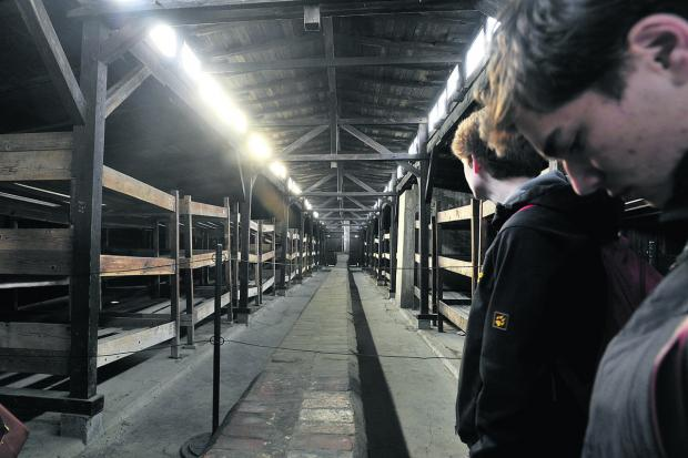 Swindon Advertiser: Youngsters survey primitive conditions in a hut at Birkenau