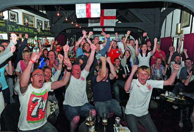 England fans celebrate a goal for the team in a packed pub