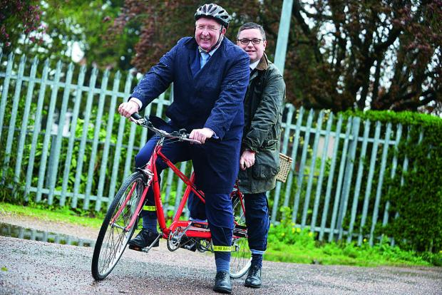 Angus Macpherson and MP Robert Buckland try out one of the tandem bikes for hire at the Salvation Army Recycles store