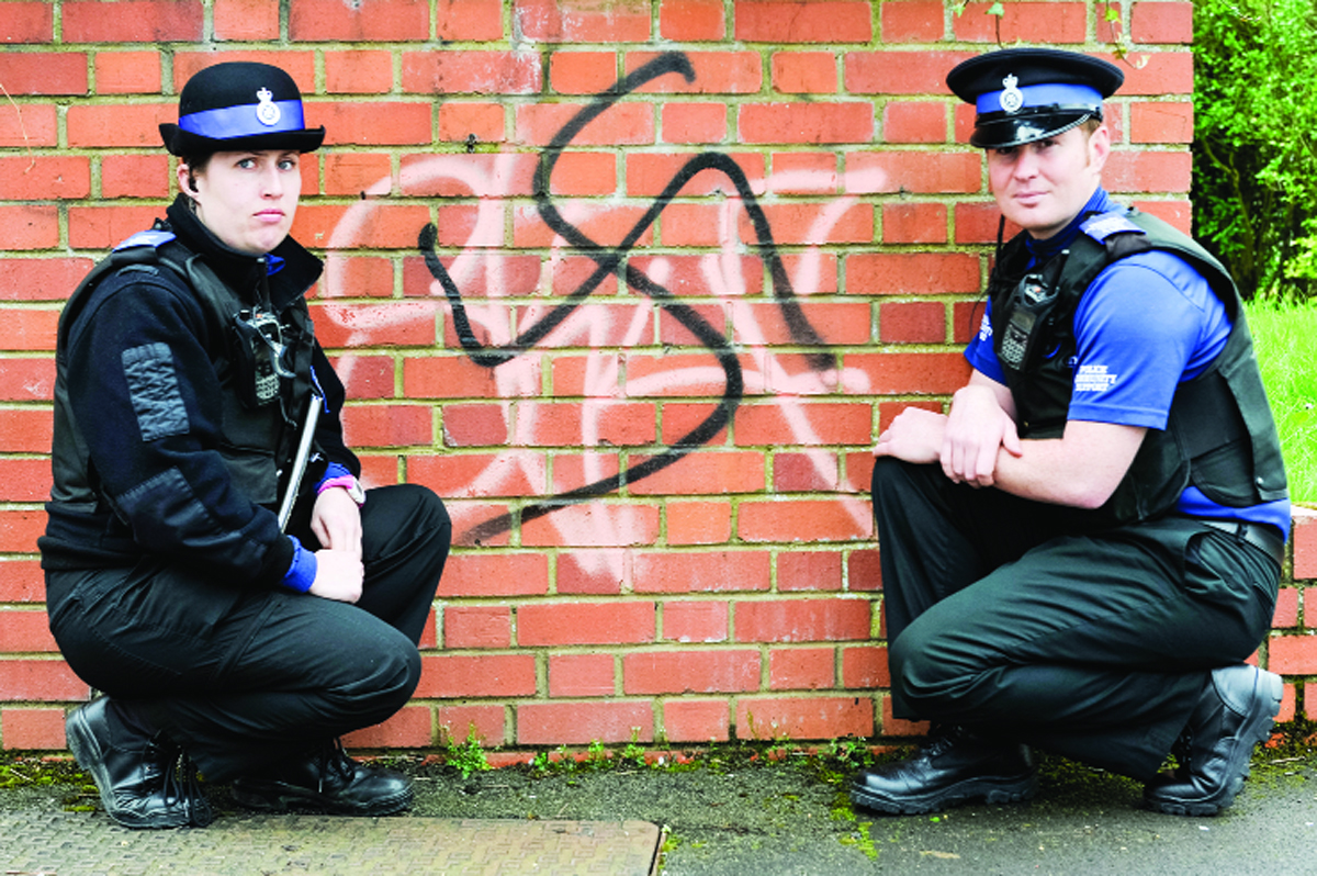 PCSOs Emma Turner and Rob Dentry with the graffiti on a wall in Walcot