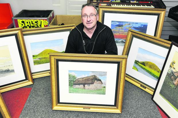 Alan Holmes with some of the paintings donated to the Goldenhar family support group to be sold