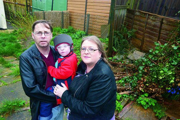 Disabled youngster Morgan Gibbons, centre, with dad Mark Willis and mum Ellen Gibbons in their back garden, which they need to convert into a safe space